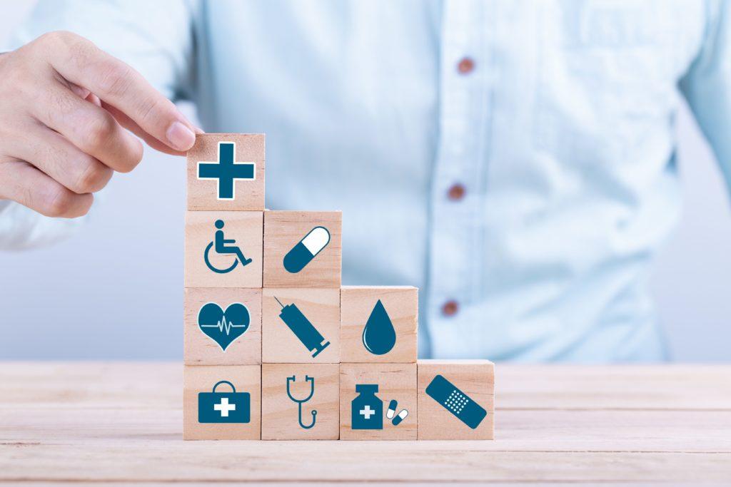 cette photo montre quelqu'un en train de faire une pile de cubes sur lesquels sont dessinés des symboles médicaux.