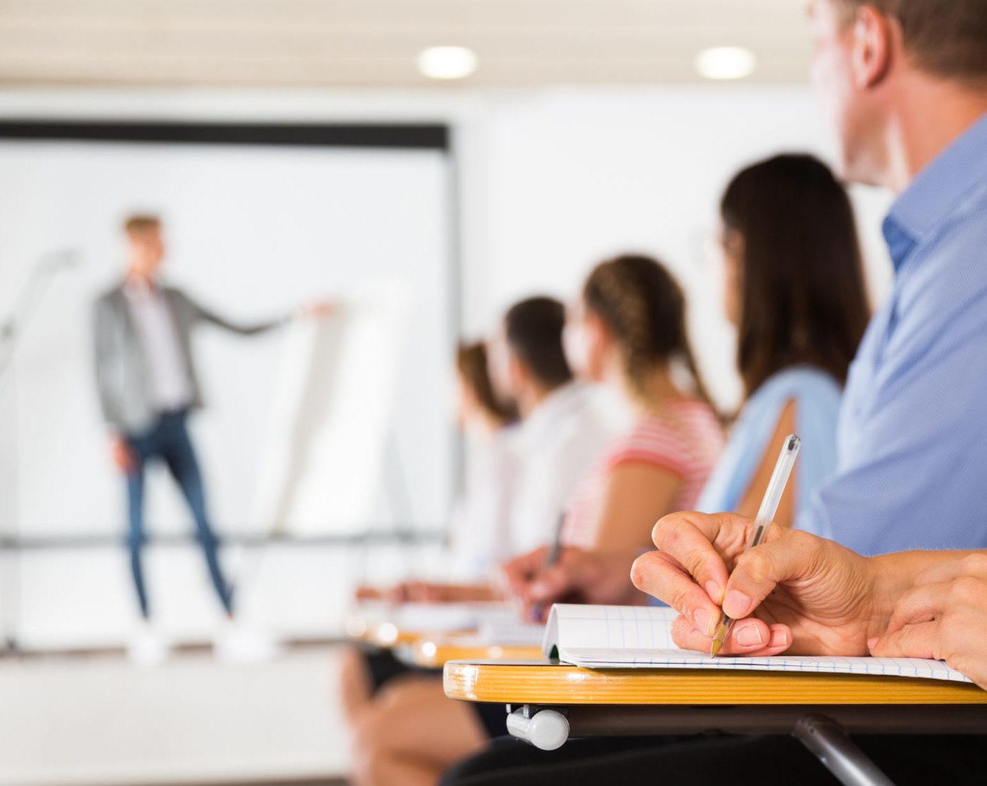 Homme présentant devant une salle de classe