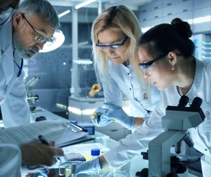 Trois cherucheurs échangeant dans un laboratoire